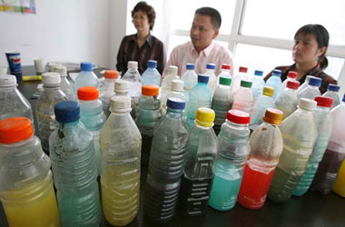 Beijing, China: Xu Jiehua (r), the wife of the detained Chinese environmental activist Wu Yilong, sits behind water samples collected by Wu Yilong from Chinese urban rivers and lakes.